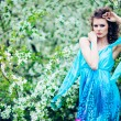 Beautiful woman in blue dress among blossom apple trees, fashion — Stock Photo
