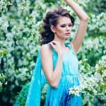 Beautiful woman in blue dress among blossom apple trees, fashion — Stock Photo