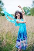 Hermosa mujer vestida de azul en el campo — Foto de Stock