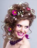 Joven feliz con flores en su pelo y maquillaje brillante — Foto de Stock