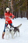Happy woman playing with siberian husky dogs in winter forest — Stock Photo
