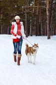 Sibirya husky köpek kış orman ile oynarken mutlu bir kadın — Stok fotoğraf