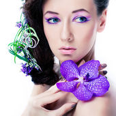 Beauty girl with orchid flowers and professional makeup — Stock Photo