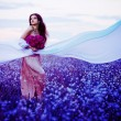 Beautiful woman in the sunset field with flowers and white fabri — Stock Photo
