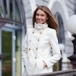 Beautiful woman in white coat on the city street  — Stock Photo