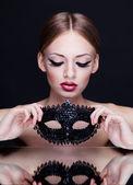 Unga skönhet kvinna med mask på mörk bakgrund — Stockfoto