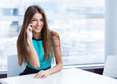 Young beauty woman sitting in a cafe and talking on the cellphone — Stock Photo