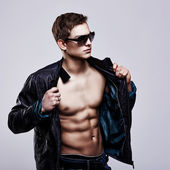 Young handsome macho man in sunglasses with open leather jacket — Stock Photo
