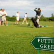 Putting green guidance board in the foreground and golf players - Stock Photo