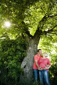 Portrait of a happy pregnant couple under a nut tree. — Stock Photo