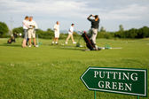 Putting green guidance board in the foreground and golf players — Stock Photo
