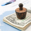 Financial concept. Old rusty weight on money and diagrams. — Stock Photo #44933015