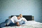 Portrait of a happy pregnant couple lying on bed — Stock Photo