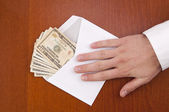 Corruption concept. Business man take a stack of money in envelo — Stockfoto