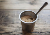 A pile of brown sugar in steel bowl with spoon, weathered wooden — Stockfoto