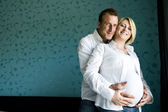 Portrait of a happy pregnant couple smiling for camera — Stock Photo