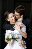 Young groom cuddle beautiful bride and kissing her. — Stock Photo