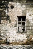 Old brick ruin wall in prague with window, and candelabras.  — Stock Photo