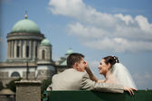 Beautiful wedding couple sit on a bench. The beauty bride pettin — Стоковое фото