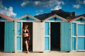 Classic beach cabins with a beautiful girl in swimming dres — Photo