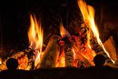 Incendio en una chimenea fuego llamas sobre un fondo negro — Foto de Stock