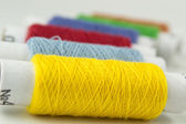 Many-coloured bobbins of thread closeup — Stock Photo