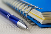 Spiral blue notebook and pen — Stock Photo