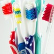 Colorful toothbrushes in a water glass — Stock Photo