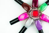 Coloured nail polish bottles stacked circle on a white background — Stock Photo