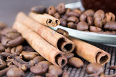 A cup of coffee with coffee beans and cinnamon sticks — Stock Photo