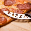 Pizza with a pizza-knife - Stock Photo