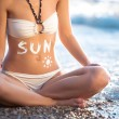 Woman belly with creme drawn sun — Stock Photo