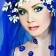 Beautiful woman with spring blue flowers — Stock Photo