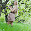 Young beautiful blonde woman in a dress in blooming apple garden — Stock Photo #22238003