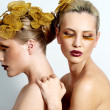 Vogue style portrait of two women with gold makeup — Stock Photo