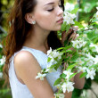Stock Photo: Beautiful girl sniffing Jasmine flowers in garden