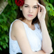 Beautiful girl with red roses in her hair — Stock Photo #22256455