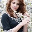 Young beautiful woman in a dress in blooming garden — Stock Photo
