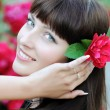 Beautiful young woman with red rose in her hair — Stock Photo
