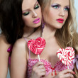 Young sexy women with heart shaped lollipops — Stock Photo