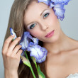 Beautiful young woman with flowers of iris — Stock Photo