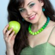 Long-haired young woman with bare shoulders holding green apple — Stock Photo