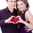 Stock Photo: Young couple forming heart shape with their hands isolated on wh