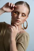Woman with gold make up and gold earrings and bracelet visible — Stock Photo