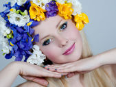 Beautiful young blonde c a wreath of irises and freesias — Stock Photo