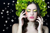 Beautiful girl with stylish makeup and yellow- green flowers aro — Stock Photo