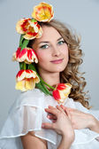 Beautiful girl in a wreath of tulips — Stock Photo