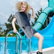 Attractive fashion blonde girl in dress near the swimming pool — Stock Photo #22525059