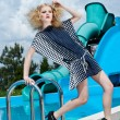Attractive fashion blonde girl in dress near the swimming pool — Stock Photo #22525105