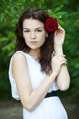 Belle fille avec des roses rouges dans les cheveux — Photo